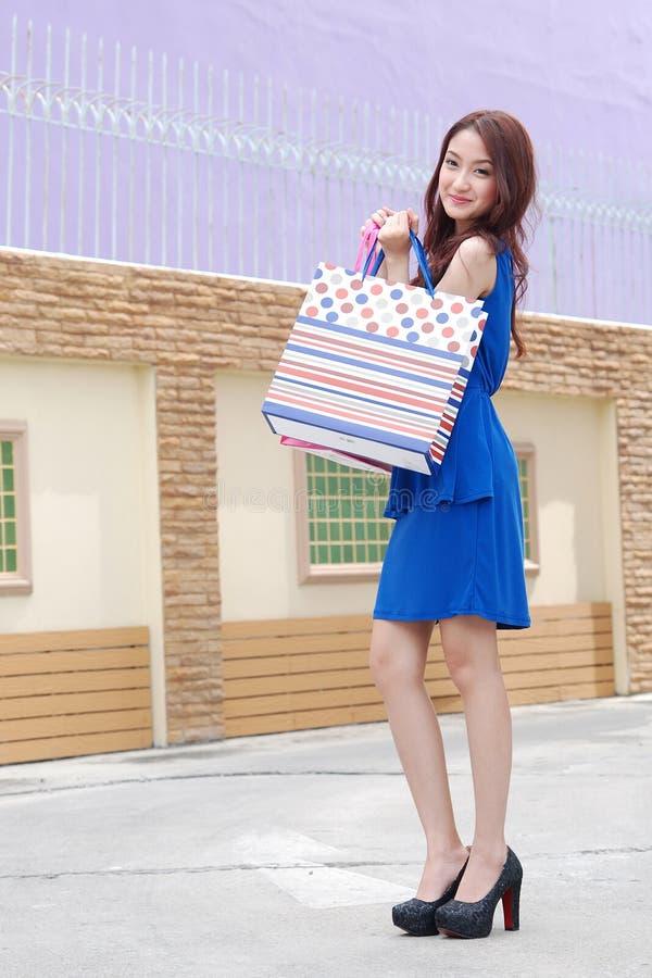 Aziatische vrouwen bij het houden van heel wat het winkelen zak in Supermarkt royalty-vrije stock foto