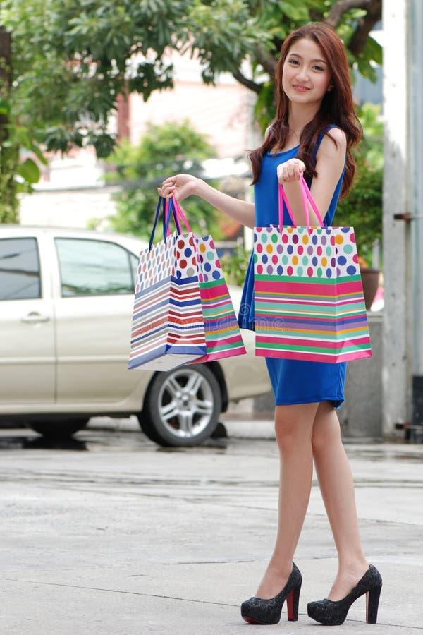 Aziatische vrouwen bij het houden van heel wat het winkelen zak in Supermarkt royalty-vrije stock afbeeldingen