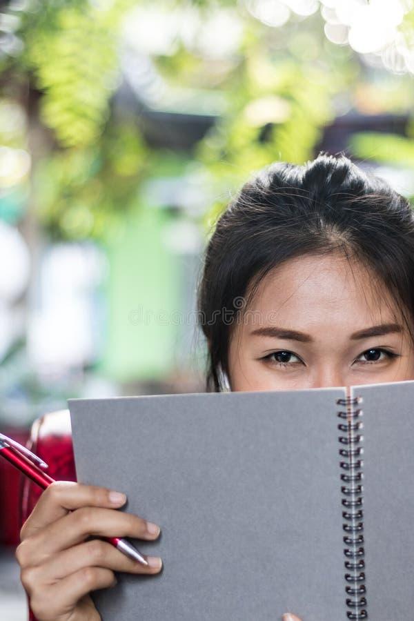 Aziatische vrouwen die agenda in notitieboekje schrijven stock fotografie