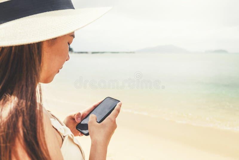 Aziatische vrouwen die in de zomer ontspannen die smartphone in vakantie op strand met behulp van royalty-vrije stock foto