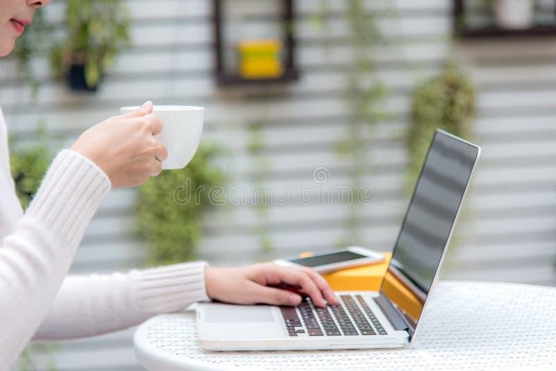 Aziatische vrouwen die hete koffie drinken en in de huistuin werken Werkt de ontspannende kou van de het werkruimte uit voor bure stock foto