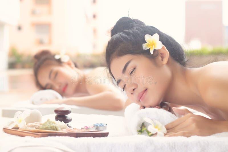 Aziatische Vrouwen die met Blije Stemming samen in The Edge van Zwembad ontspannen Wellnesslichaamsverzorging en kuuroord aromath stock afbeelding