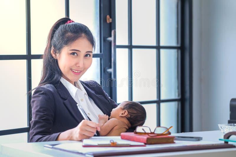 Aziatische vrouwen die in zaken werken en kinderenhuis opheffen royalty-vrije stock afbeelding