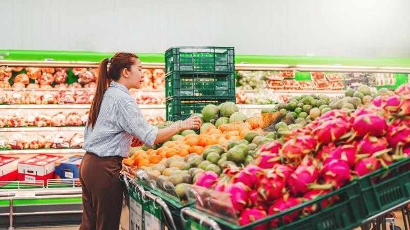 Aziatische vrouwen het winkelen Gezonde voedselgroenten en vruchten in supermarkt stock foto's