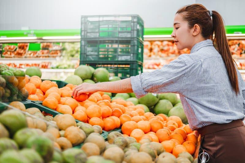 Aziatische vrouwen het winkelen Gezonde voedselgroenten en vruchten in supermarkt stock foto