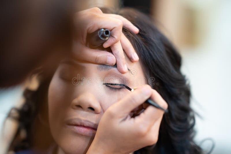 Aziatische vrouwen model valse wimpers tijdens samenstellingszitting De grimeur past een zwarte eyeliner met de borstel op ooglid stock fotografie