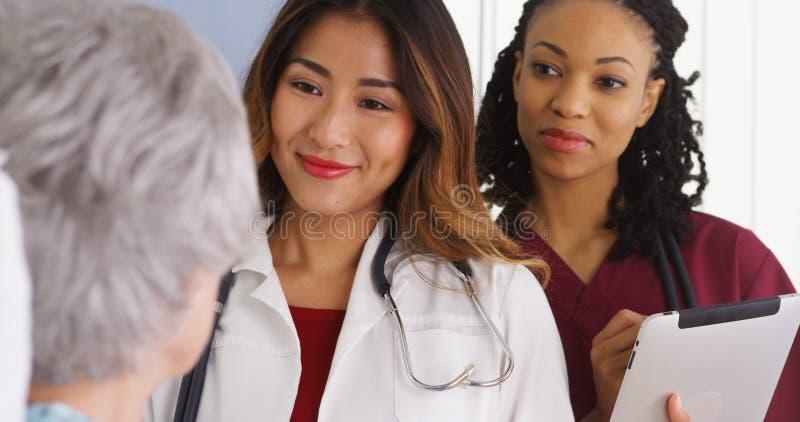 Aziatische vrouwenarts en verpleegster die aan bejaarde patiënt in bed spreken royalty-vrije stock foto's