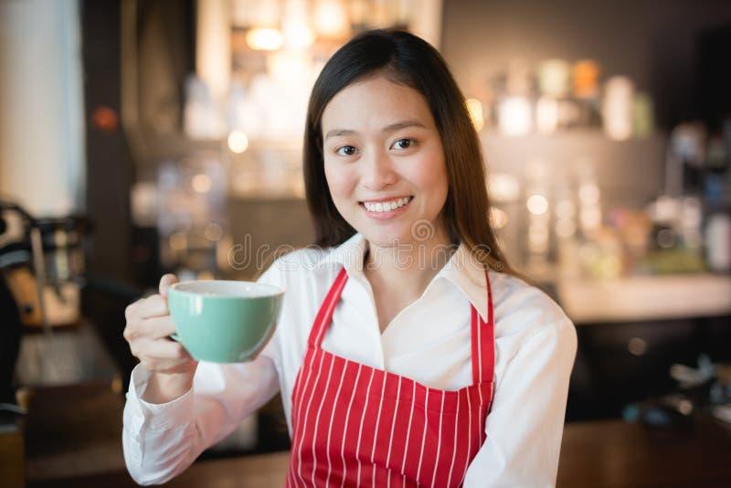 Aziatische vrouwenbarista die met een kop van koffie in haar hand glimlachen, Koffieverkopers levert koffie aan klanten, uitsteke stock fotografie