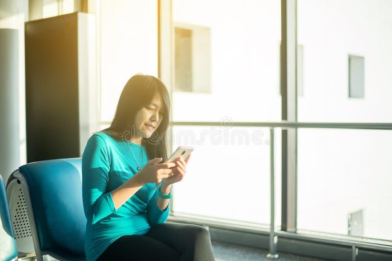 Aziatische vrouwenpassagier die mobiele telefoon houden en vlucht of online controle en reisontwerper bij internationale luchthav royalty-vrije stock afbeelding