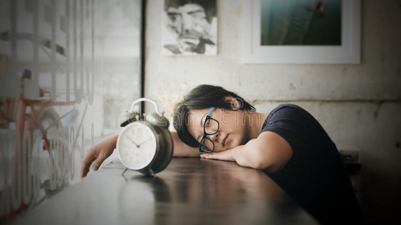 Aziatische vrouwenslaap in de koffie van de koffiewinkel met klok stock fotografie