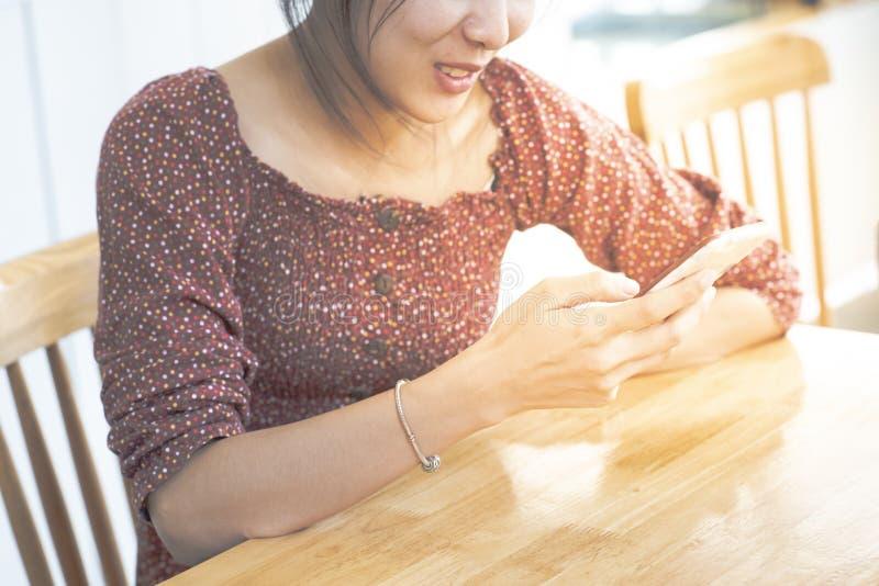 Aziatische vrouwentiener in toevallige kleding met glimlach op het gebruiks slimme mobiele telefoon van de gezichtshand in koffie royalty-vrije stock afbeeldingen