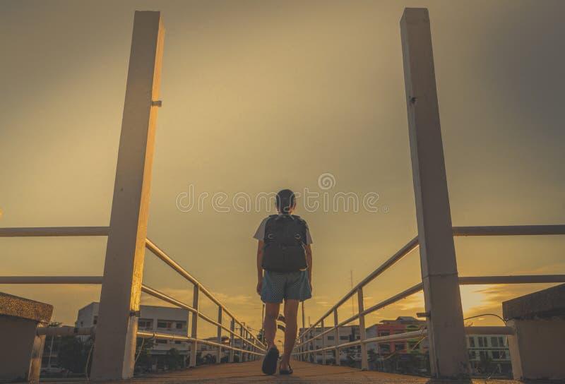 Aziatische Vrouwentoerist die alleen met rugzak op de brug in de stad in de avond op zonsondergang met gele hemel lopen Gang weg royalty-vrije stock afbeeldingen