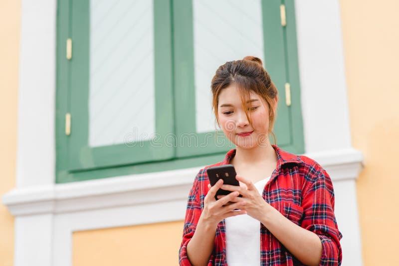 Aziatische vrouwentoerist die backpacker en smartphone glimlachen gebruiken die alleen reizen royalty-vrije stock foto's