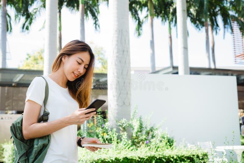 Aziatische vrouwentoerist die backpacker en smartphone glimlachen gebruiken die alleen reizen stock afbeeldingen