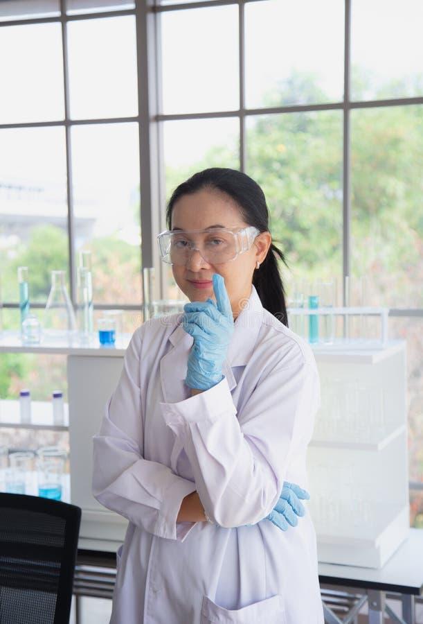 Aziatische vrouwenwetenschapper die glazentribune in laboratoriumruimte dragen stock fotografie