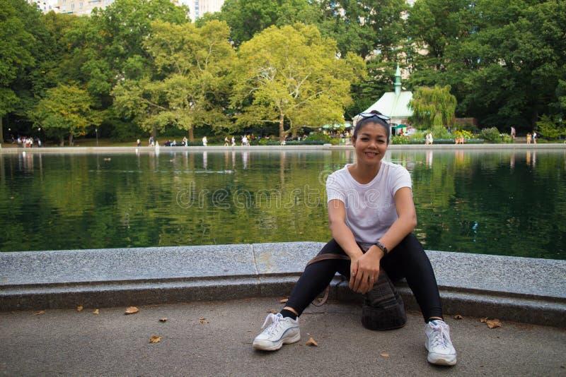 Aziatische Vrouwenzitting door Behoudend Water in Central Park stock fotografie