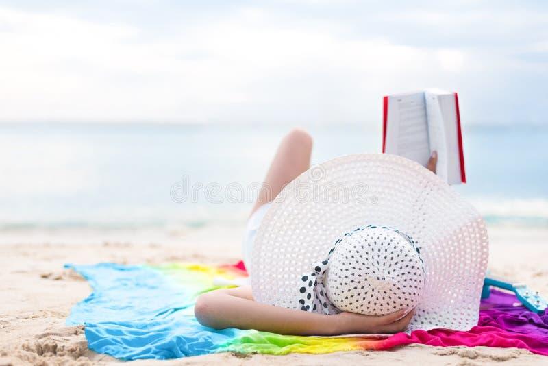 Aziatische vrouwenzon die en boeken in vakantie baden lezen bij strand B stock fotografie