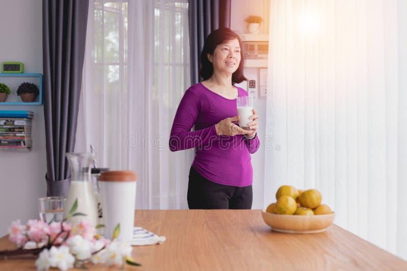 Aziatische wat melk drinken en Bejaarden die uit vensters kijken royalty-vrije stock afbeeldingen