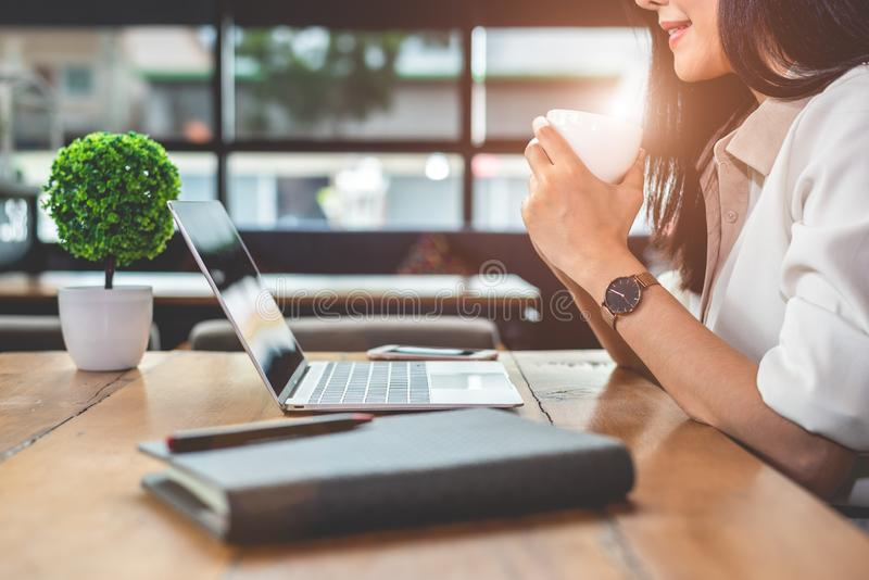 Aziatische werkende vrouw gebruikend laptop en drinkend koffie in koffie Mensen en levensstijlenconcept Technologie en bedrijfsth stock foto's