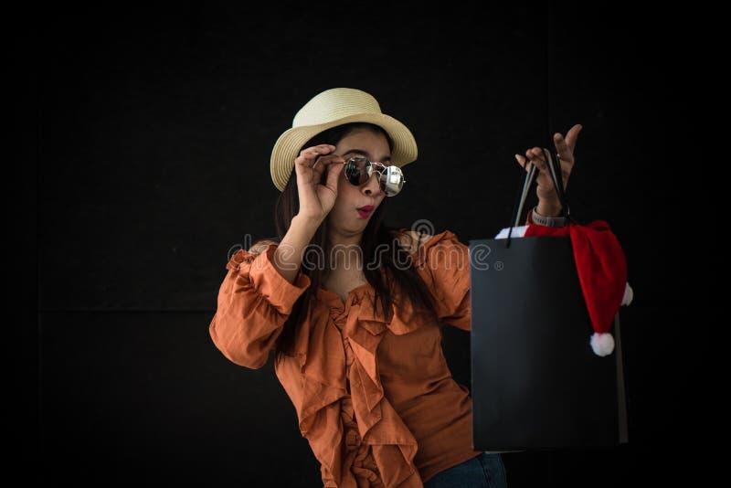 Aziatische winkelende die vrouw met Black Friday-het winkelen zak en Santa Claus-hoed binnen op zwarte achtergrond wordt verrast  stock afbeelding