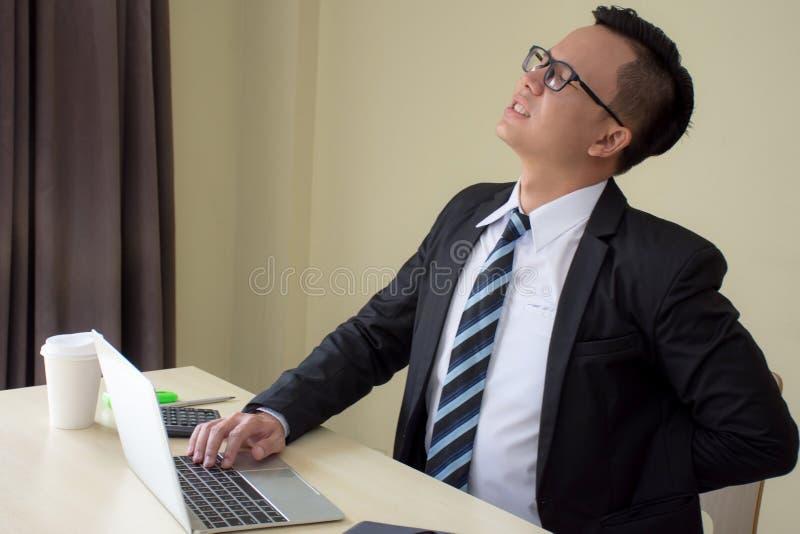 Aziatische zakenlieden in een kostuum die hard en het pijnlijke raken terug met gekwetste expressionat na lange werkuren werken v stock foto's