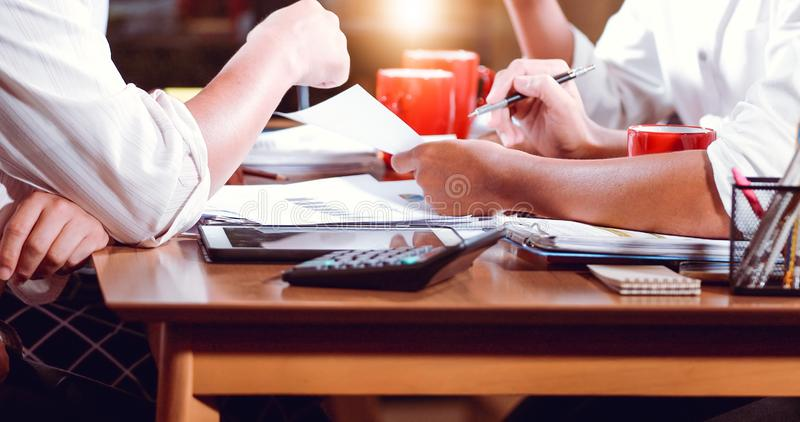 Aziatische zakenlieden en onderneemstersanalysedocumenten op bureaulijst met laptop computer en grafiek financieel diagram die bi stock foto