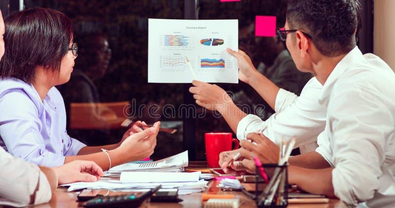 Aziatische zakenlieden en onderneemstersanalysedocumenten op bureaulijst met laptop computer en grafiek financieel diagram die bi royalty-vrije stock afbeeldingen