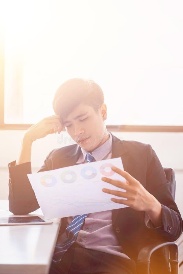 Aziatische zakenman die de afdelingsgrafiek kijken stock fotografie