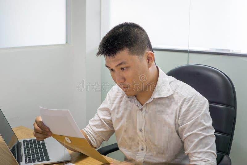 Aziatische zakenman die financieel aantal op document lezen stock fotografie