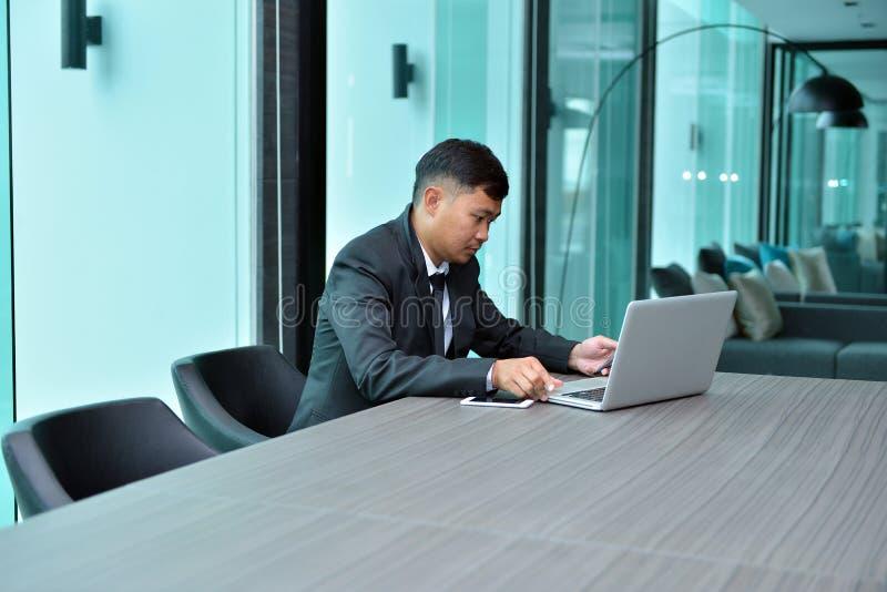 Aziatische Zakenman die laptop in een conferentieruimte met behulp van stock foto's