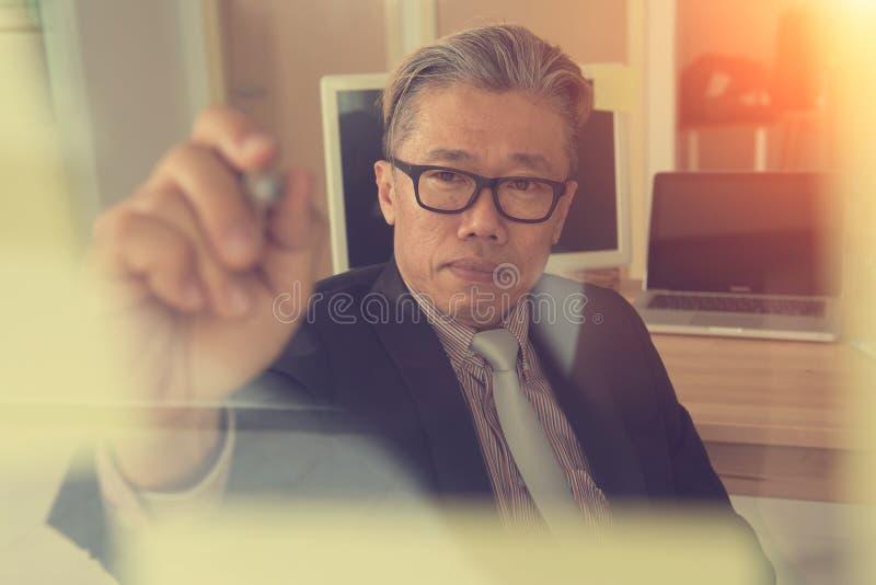 Aziatische zakenman die op glasmuur schrijven royalty-vrije stock afbeelding