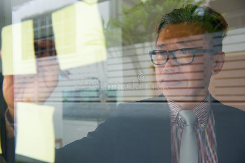 Aziatische zakenman die op glasmuur schrijven stock fotografie
