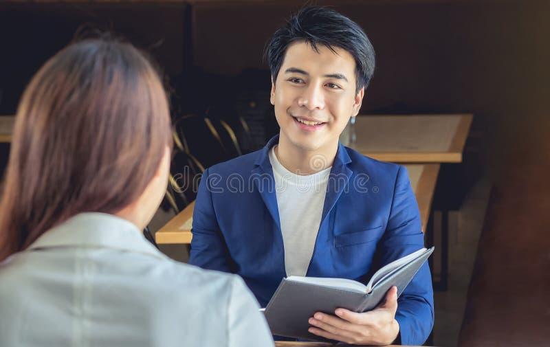Aziatische zakenman die in vriendschappelijk glimlachen om bedrijfsbespreking te ontmoeten stock foto