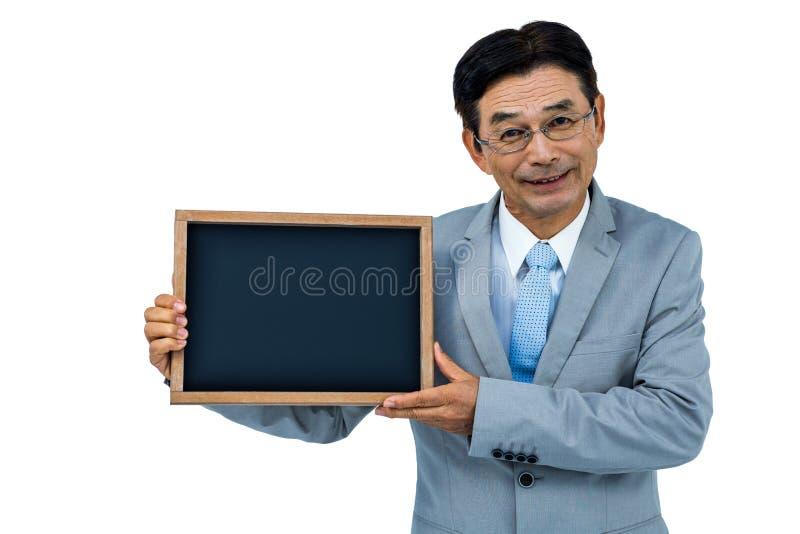 Aziatische zakenman die zwarte raad tonen royalty-vrije stock foto's