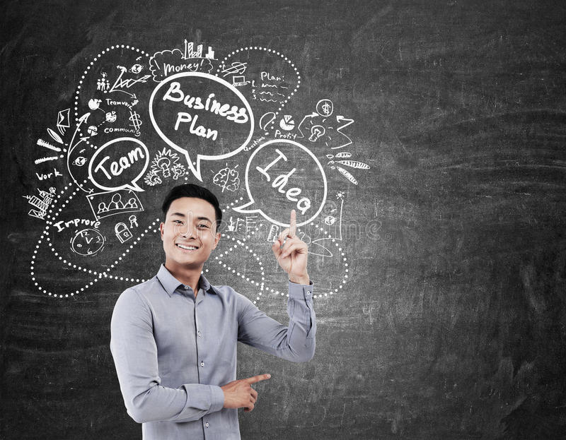 Aziatische zakenman en businessplanpictogrammen op bord stock foto's