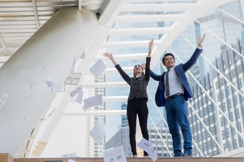 Aziatische zakenman en onderneemster die document in de lucht werpen en op twee handen aan gevierd voor succesvol in opdracht oph royalty-vrije stock afbeeldingen