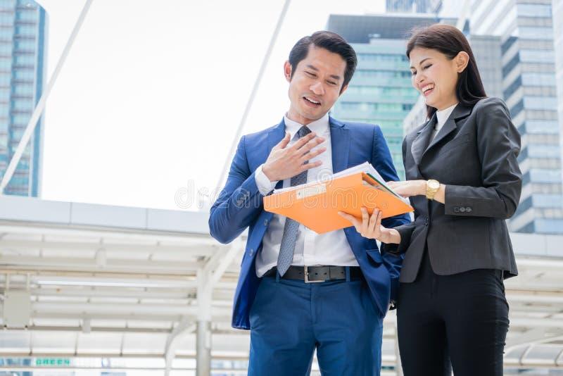 Aziatische zakenman en zakenvrouw die in de stad staan en praten over zakelijk succes stock foto's