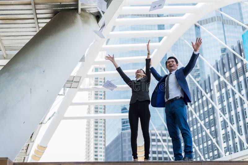 Aziatische zakenman en zakenvrouw die papier in de lucht gooien en twee handen opsteken om te vieren voor succes stock fotografie