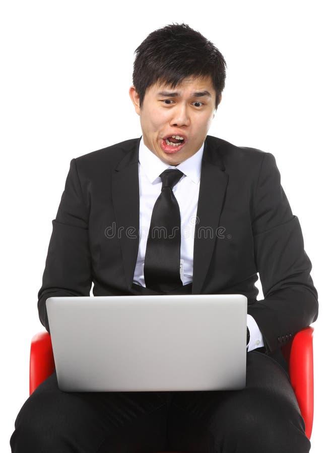 Aziatische zakenman geschokte verrassing door laptop computer stock afbeelding