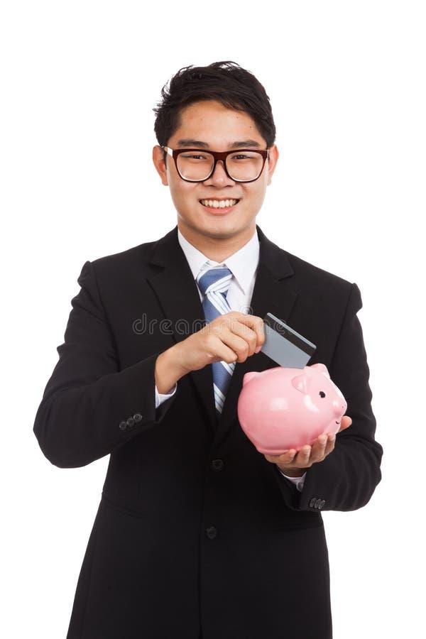 Aziatische zakenman gezette creditcard aan spaarvarken royalty-vrije stock foto's