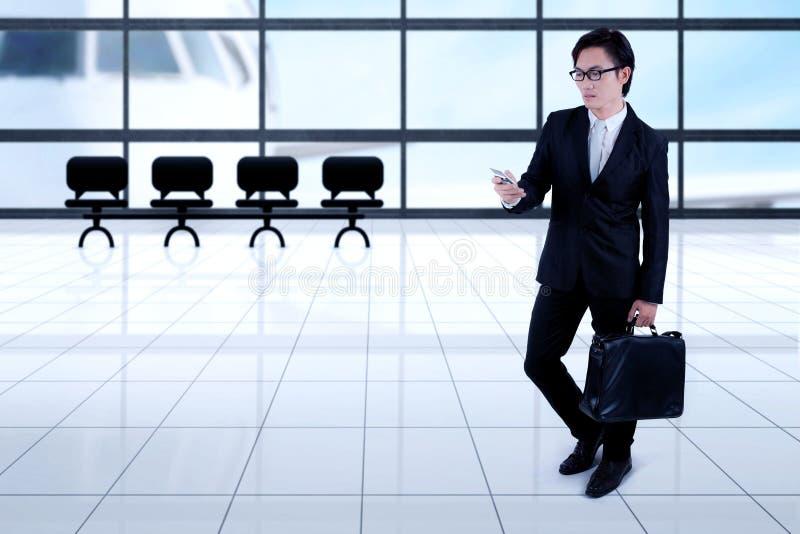 Aziatische zakenman met smartphone in de luchthaven stock fotografie