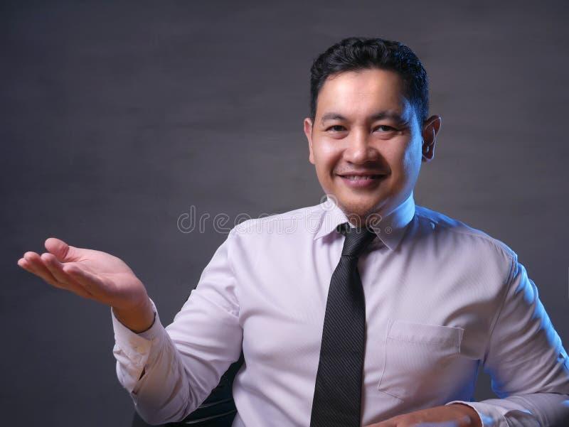 Aziatische Zakenman Presenting Something aan Zijn Kant met Exemplaarruimte royalty-vrije stock fotografie