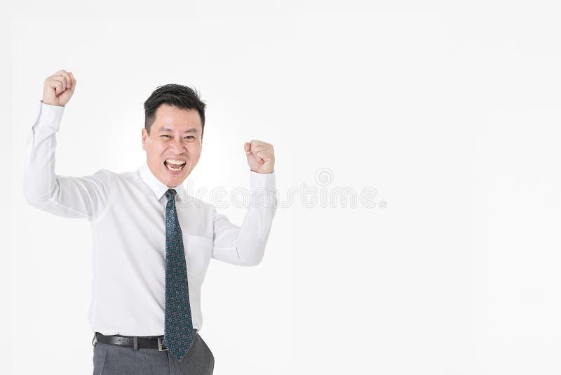 Aziatische zakenman in toevallige overhemds waarnemende winnaar vrolijk voor Com royalty-vrije stock foto