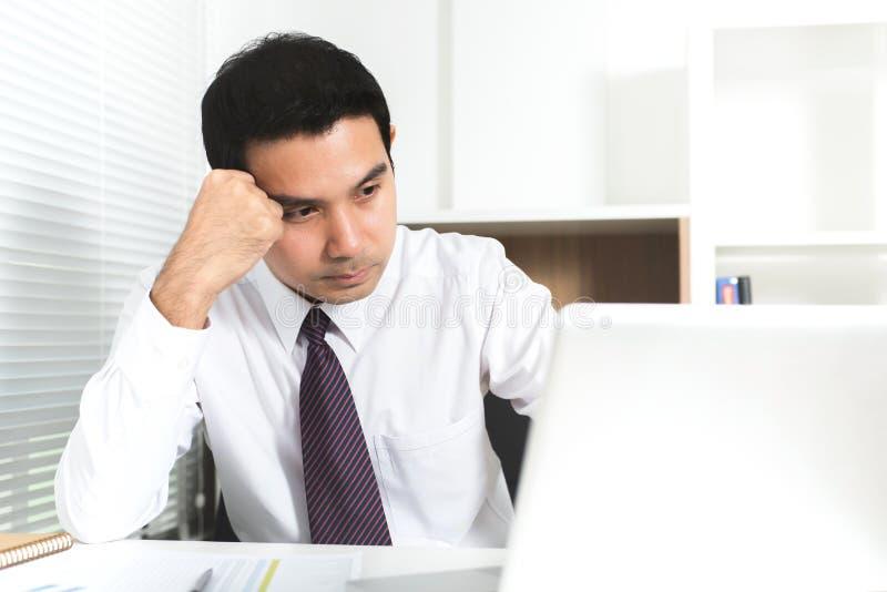 Aziatische zakenman worden die die op het werk wordt beklemtoond royalty-vrije stock afbeelding