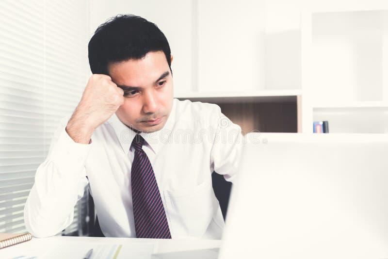 Aziatische zakenman worden die die op het werk wordt beklemtoond stock foto