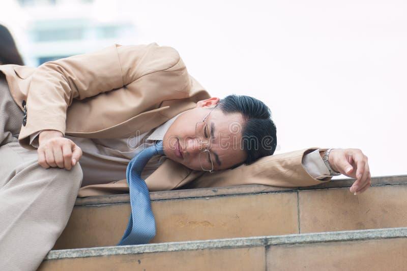 Aziatische zakenmanslaap op bank buiten stock afbeelding
