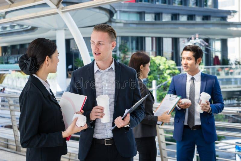 Aziatische zakenvrouw praat over de toekomst van het bedrijfsleven met Kaukasische zakenman royalty-vrije stock fotografie