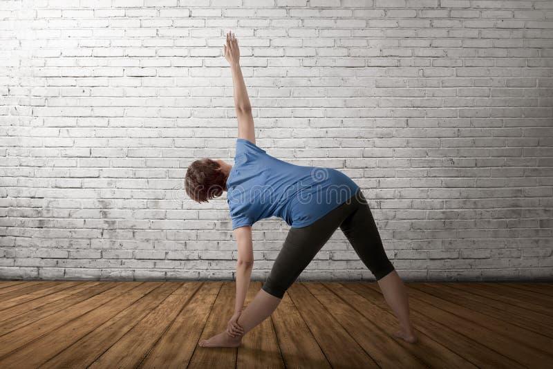 Aziatische zwangere moeder die gymnastiek in lege ruimte doen royalty-vrije stock fotografie