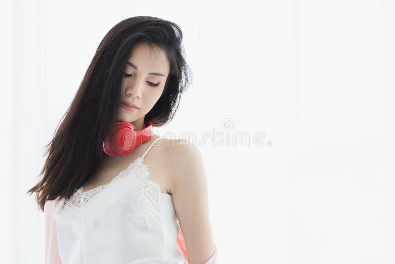 Aziatische zwarte haarvrouw die rode hoofdtelefoon dragen royalty-vrije stock afbeeldingen