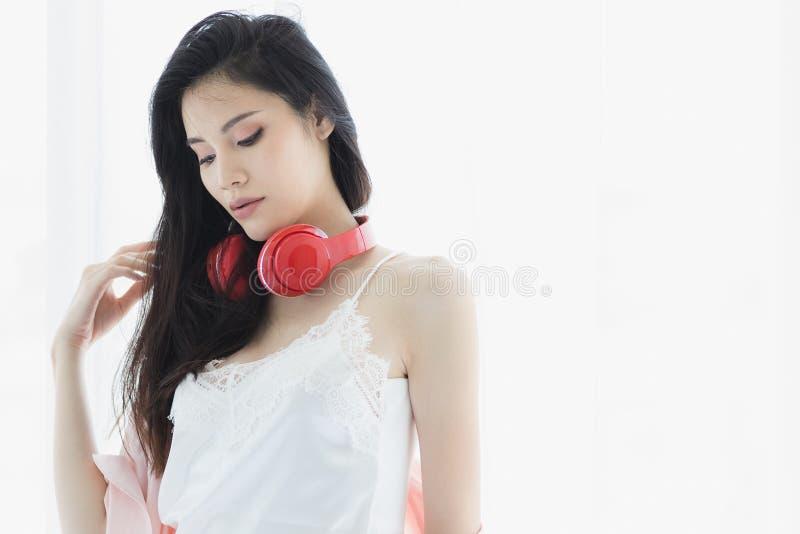 Aziatische zwarte haarvrouw die rode hoofdtelefoon dragen stock fotografie